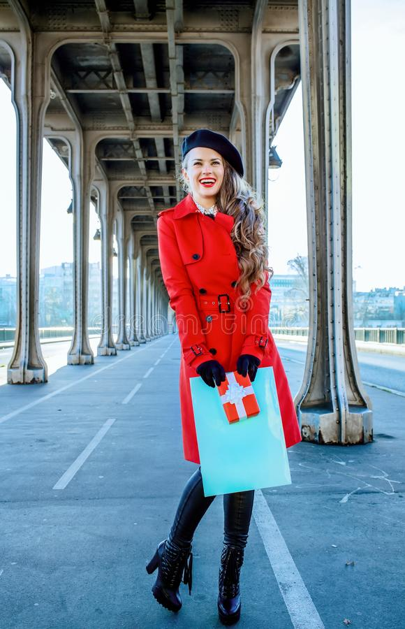 Woman in Paris holding shopping bag and Christmas present box. Bright in Paris. Full length portrait of happy elegant woman in red trench coat on Pont de Bir royalty free stock image