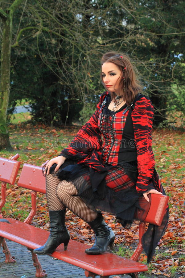 Woman in the park. Beautiful young gothic woman sitting on a bench in a park in the city stock image