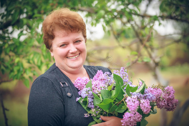Woman in park with a big bouquet of a lilac. Happy woman in park with a big bouquet of a lilac stock photos