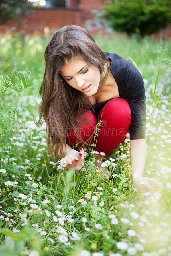 Woman in park gather spring flowers stock photo