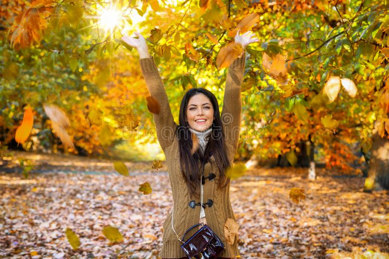 Woman in a park during golden autumn time. A happy woman in a park during golden autumn time throws colorful leafs in the air and enjoys the day royalty free stock photography