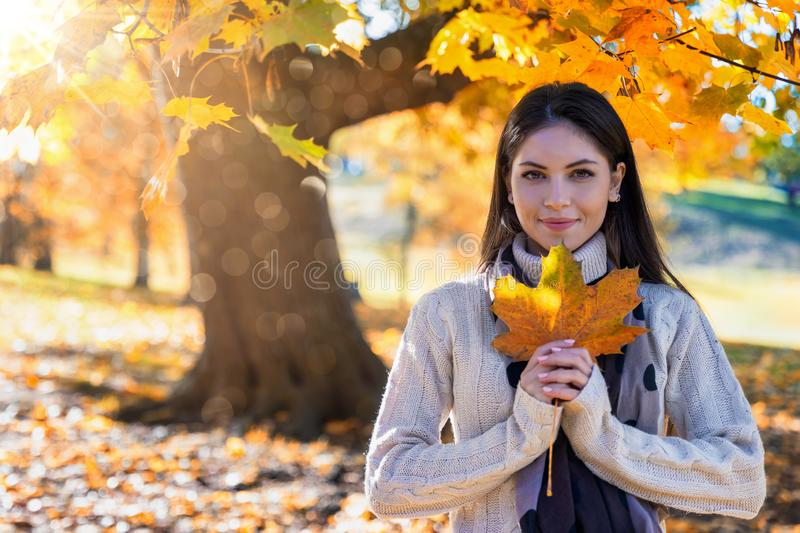Woman in a park holding a colorful leaf in her hand. Beautiful woman in a park during autumn season holding a colorful leaf in her hand royalty free stock images