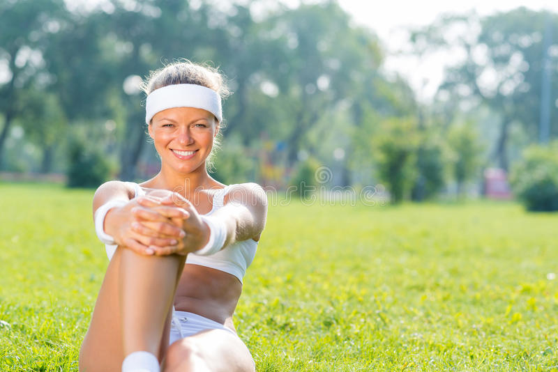 Woman in park. Young fitness girl sitting in park on green grass royalty free stock photos