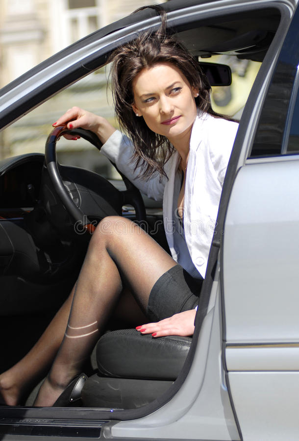Woman parks the car. Brunette woman looks round and parks the car back stock photography