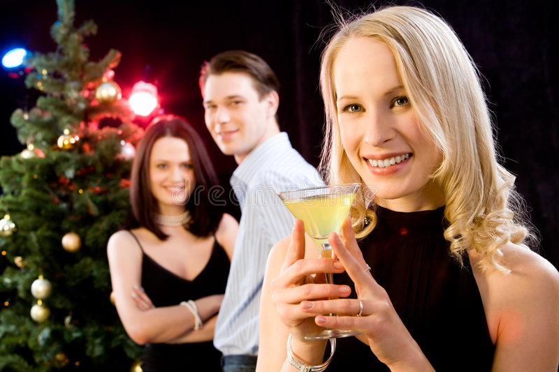 Woman at a party. Portrait of beautiful blond woman in her black dress on the background of couple and christmas-tree royalty free stock images