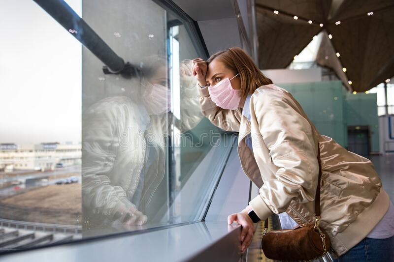 Woman passenger in protective mask looking at window at almost empty airport terminal due to coronavirus pandemic. Sad woman passenger in protective mask looking royalty free stock photo
