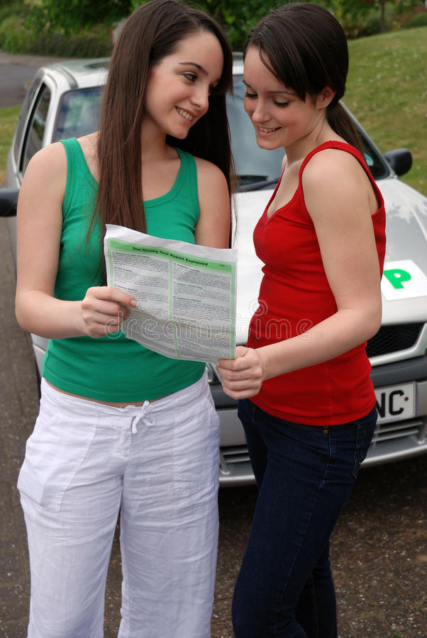 Woman passing driving test. Closeup of smiling woman showing successful driving test results to friend with motor car in background stock images