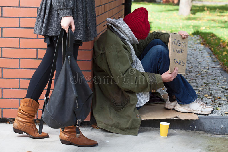 Woman passing by the homeless stock images