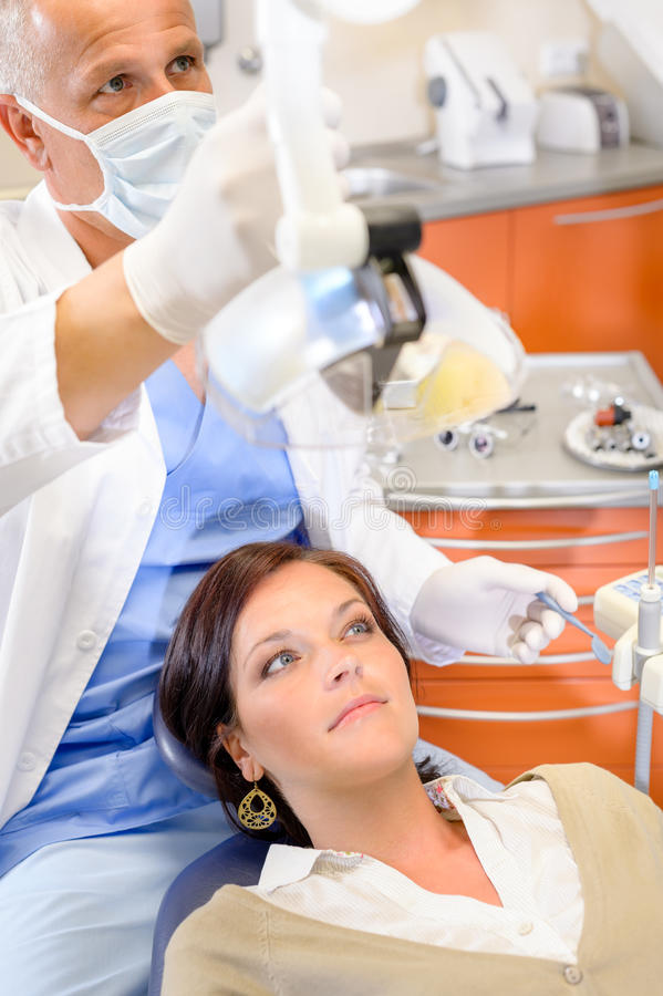 Woman patient at dental hygienist surgery. Woman patient at dental surgery with male hygienist stomatology clinic royalty free stock photo