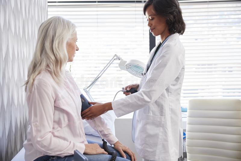 Woman Patient Having Blood Pressure Taken By Female Doctor In Office stock photography