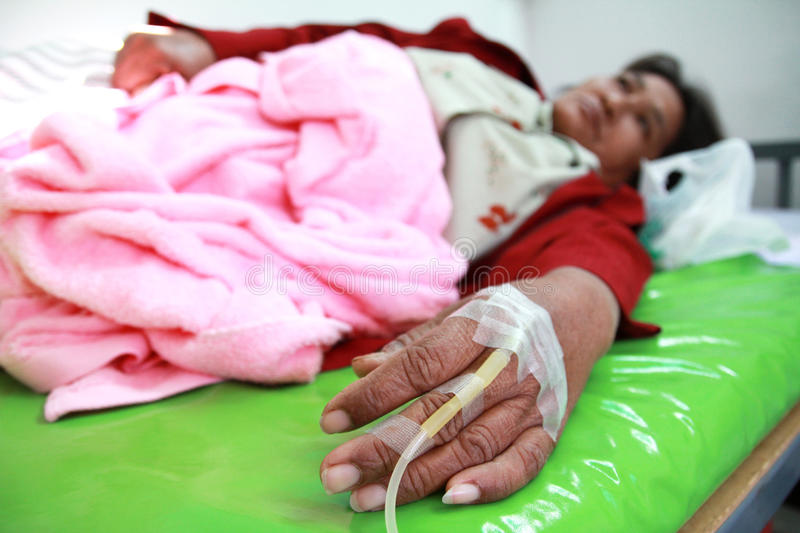 Woman patient in hospital with saline intravenous stock images