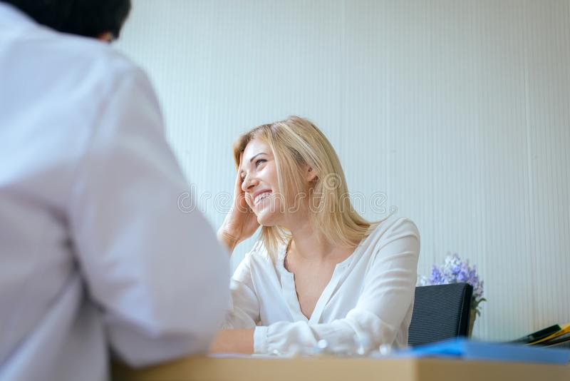 Woman patient talking with senior man doctor examining and follow up treatment at hospital ward,Happy and laughing royalty free stock photo