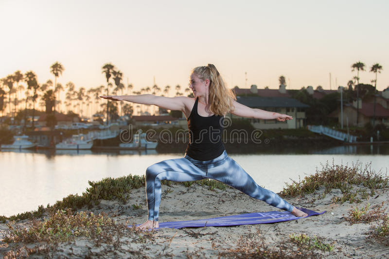 Woman in pattern tights holding a strong base at sunrise. royalty free stock image