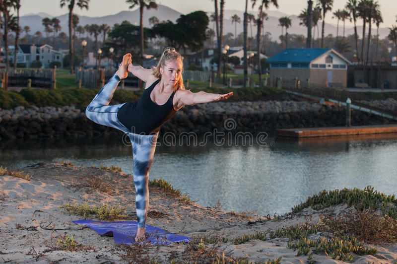 Woman in pattern tights working flexibility and balance at sunrise. stock images