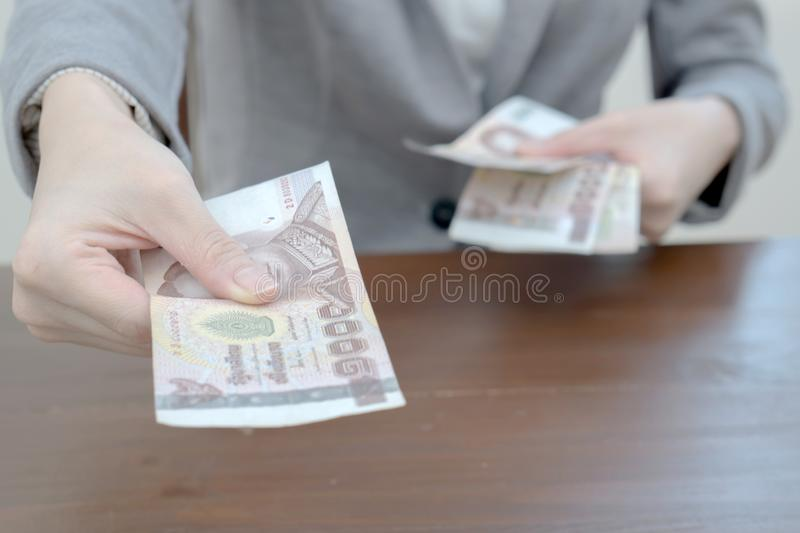 Woman is paying In cash with banknotes stock images