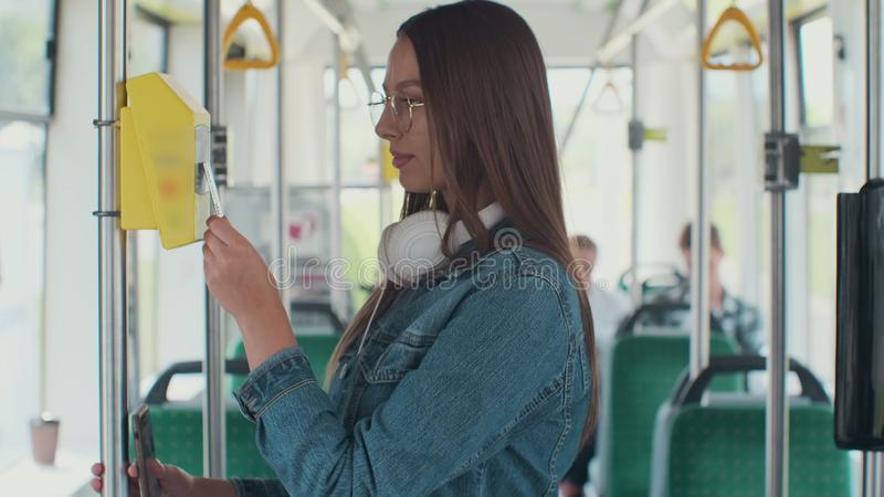 Woman paying conctactless with bank card for the public transport in the tram. Woman paying conctactless with bank card for the public transport in the tram royalty free stock photos