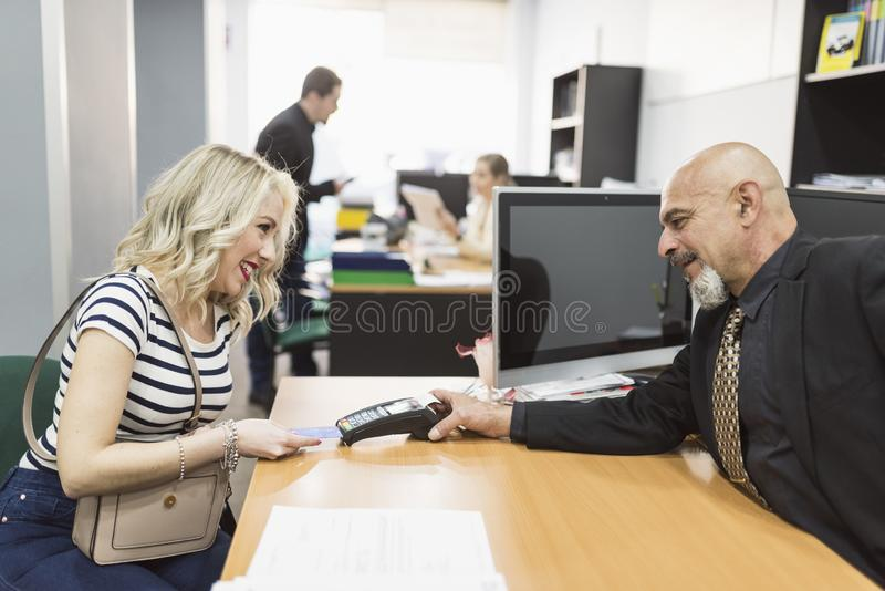 Woman paying with credit card in company office royalty free stock photography