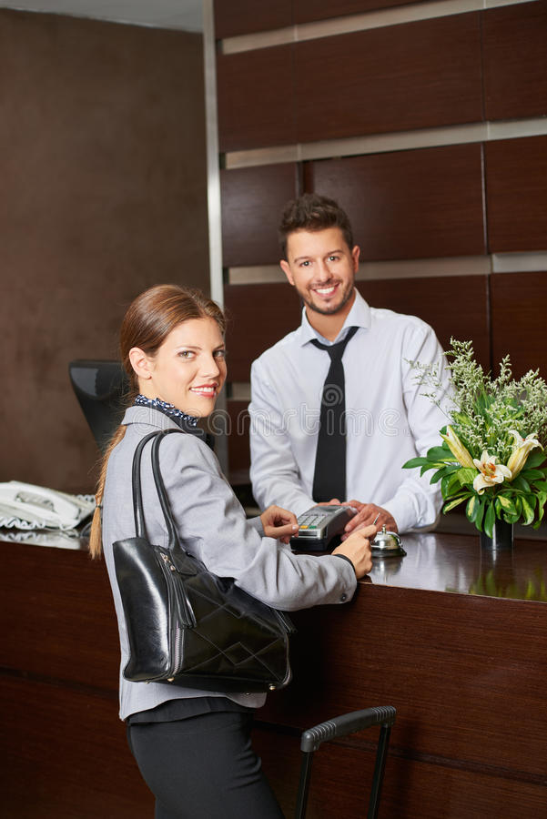 Woman paying with credit card in hotel stock photography