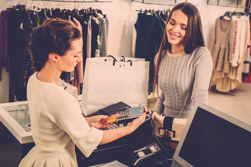 Woman paying with credit card in s showroom. Happy women customer paying with credit card in fashion showroom stock photos