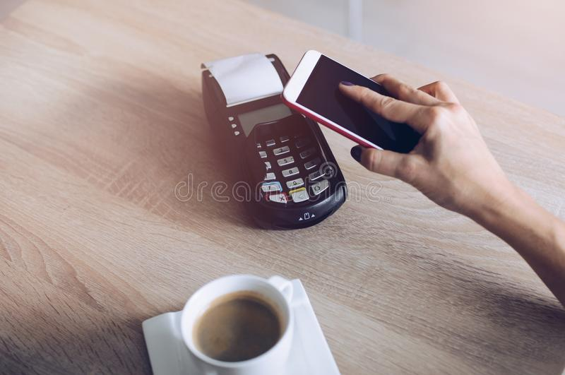 Woman paying with mobile phone. For coffee in cafe. Mobile phone payment stock photo