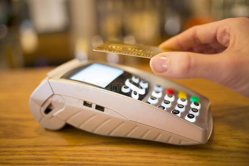 Woman paying with NFC technology on credit card, r. Female hand wallet payment shop stock photography