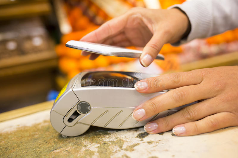 Woman paying with nfc technology on mobile phone, shopping, supermarket. Female electronic payment close-up cell phone hand shop electronic reader stock images