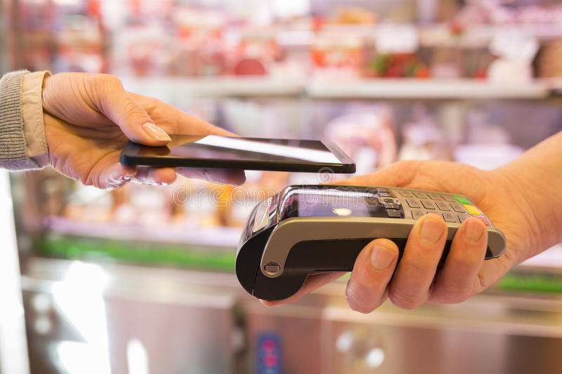 Woman paying with NFC technology on mobile phone, in supermarket. Female paying cellphone shop butcher royalty free stock photos