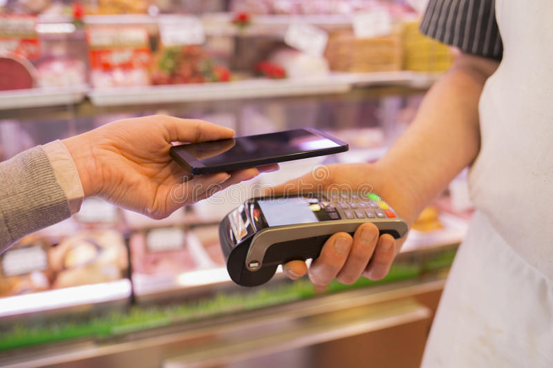 Woman paying with NFC technology on mobile phone, in supermarket. Female paying cellphone shop butcher royalty free stock image