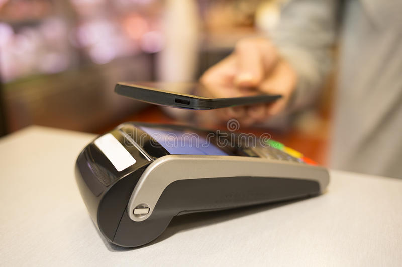 Woman paying with NFC technology on mobile phone, in supermarket. Female paying cellphone shop butcher royalty free stock photography