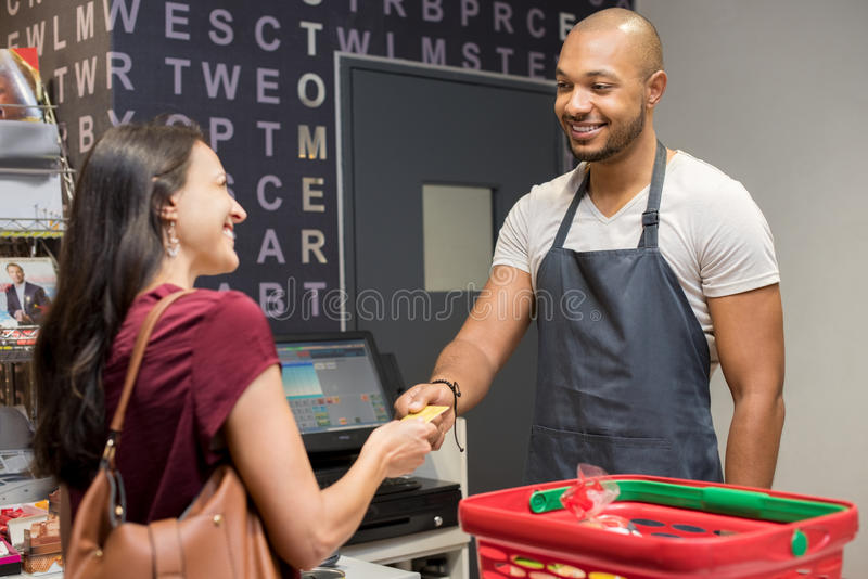Woman paying at supermarket stock image