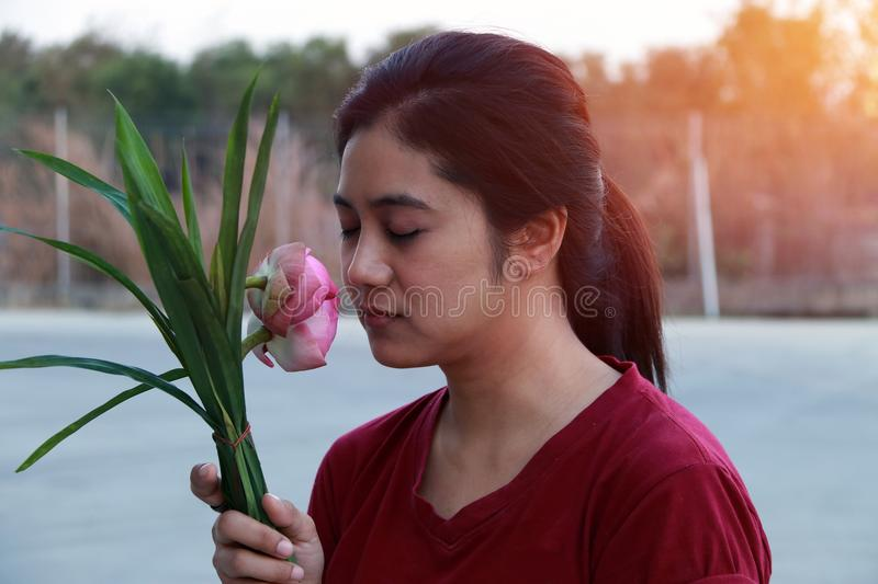 Woman peacefully smelling the pink lotus in bouquet. Lady in dark red short sleeve shirt and flower in hand royalty free stock photos
