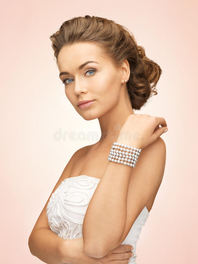 Woman with pearl earrings and bracelet. Beautiful bride wearing pearl earrings and bracelet stock images