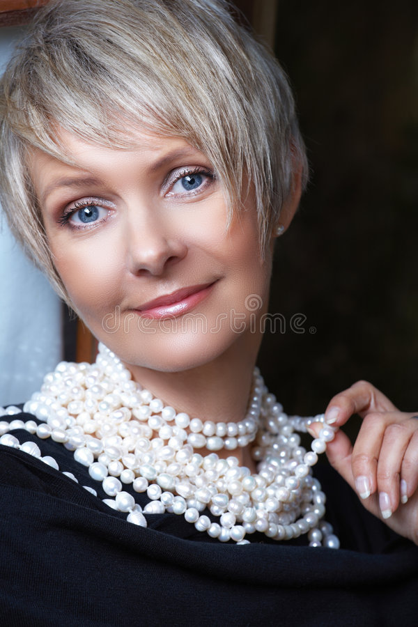 Woman in pearls in her 40s. Beautiful happy woman in her mid 40s with blond short hair wearing fresh water pearls
