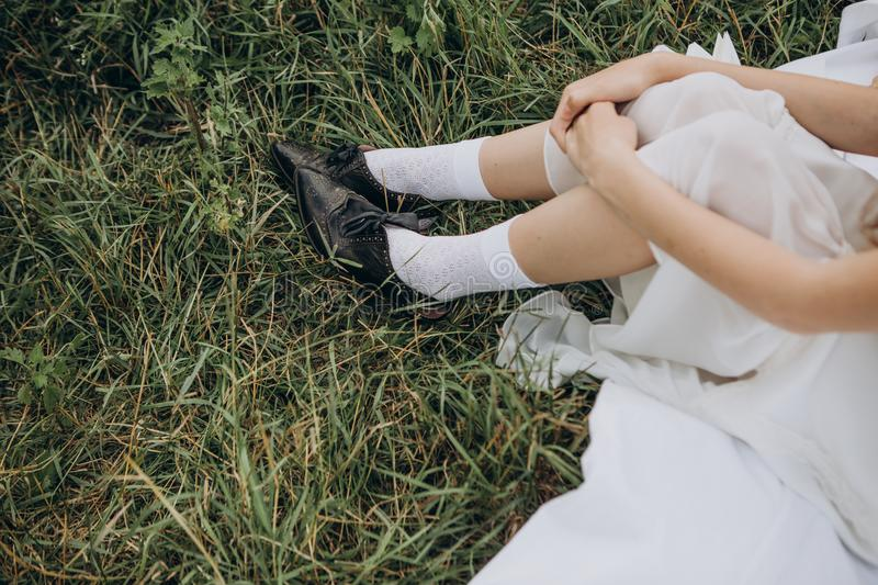 Woman peasant sitting grass white dress black shoes. Woman peasant sitting on grass in white dress and black shoes stock photos