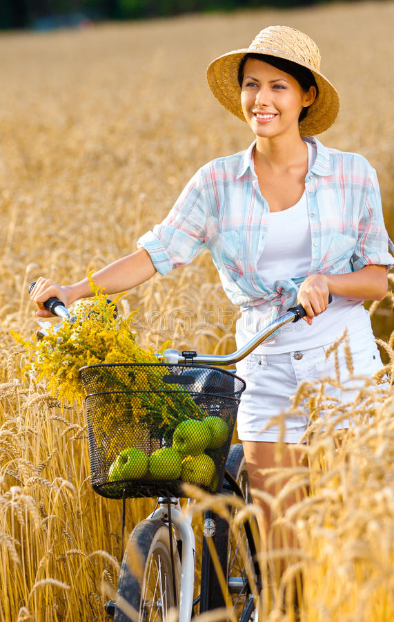 Free Woman Pedals Cycle With Apples And Flowers In Rye Field Royalty Free Stock Photo - 40736725