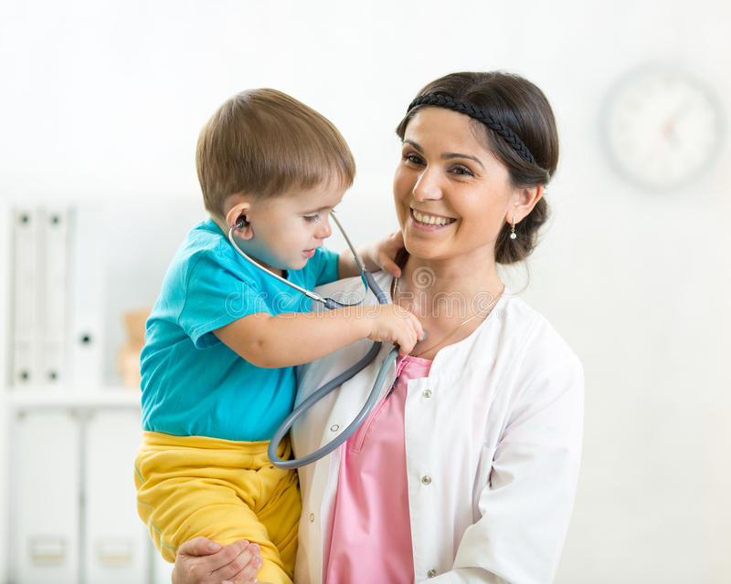 Woman pediatrician holding in her arms kid boy patient in office royalty free stock photography