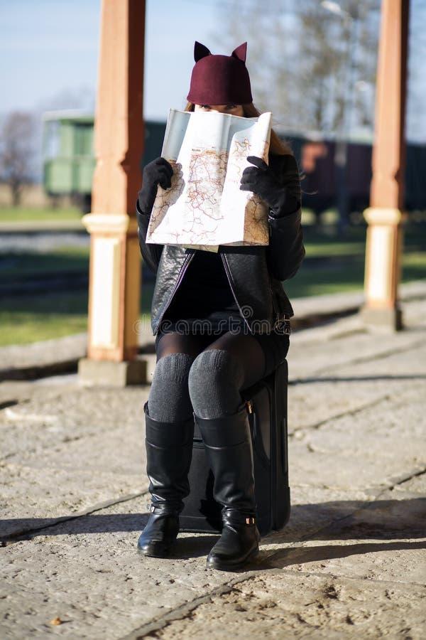 Woman peek over map look straight. Woman on baggage peek over map look straight stock images