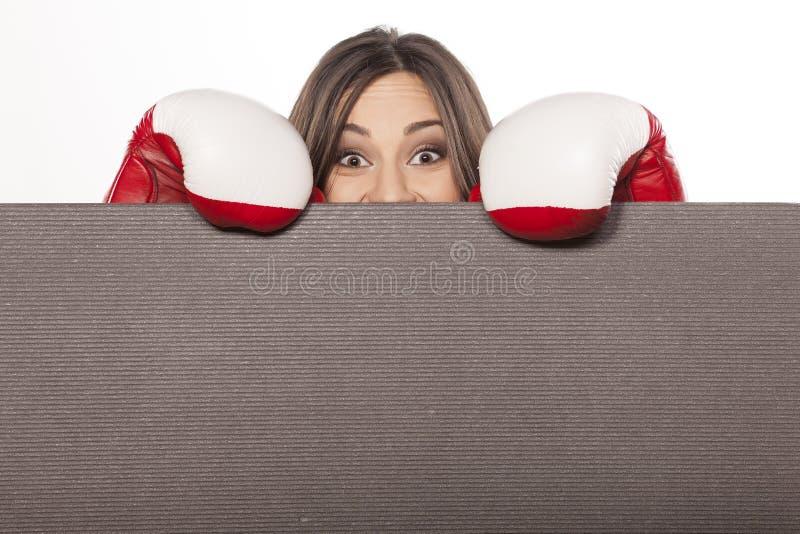 Woman peeking. Happy young woman with boxing gloves peeking behind an empty board stock photos