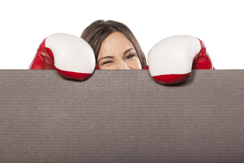 Woman peeking. Happy young woman with boxing gloves peeking behind an empty board stock images