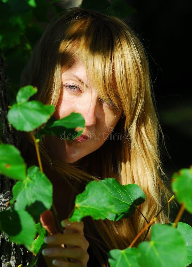 Woman peeking through leaves royalty free stock photos