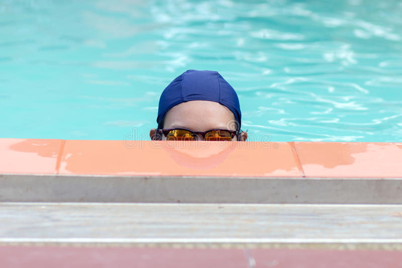 Woman peeking out of the pool royalty free stock photography