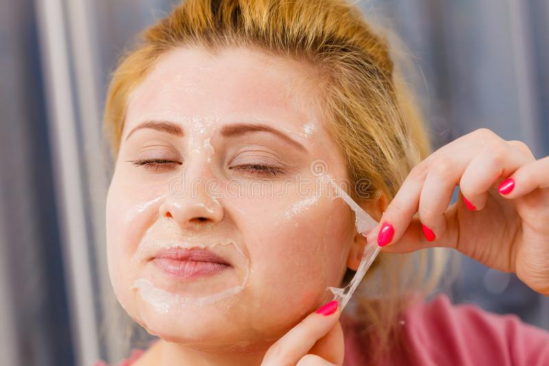 Woman peeling off gel mask from face stock image