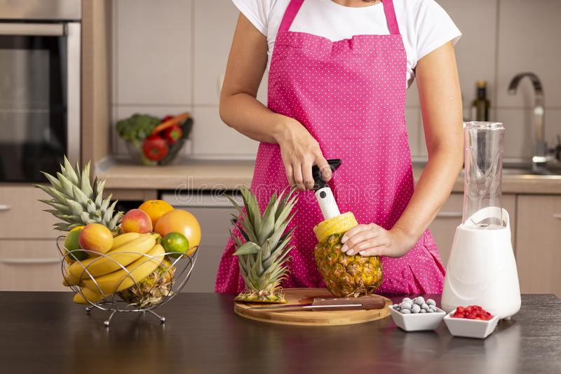 Woman using a pineapple cutter stock image