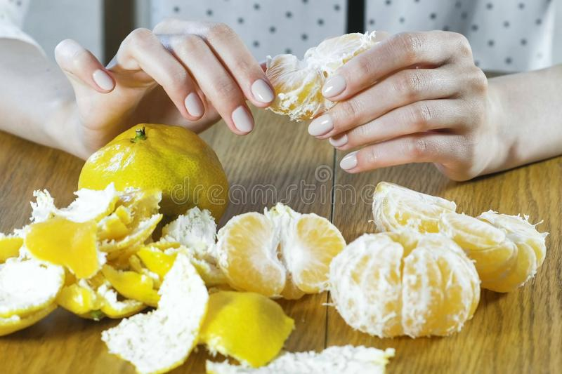 Woman peels a tangerine by hands. Hands close up. royalty free stock photos