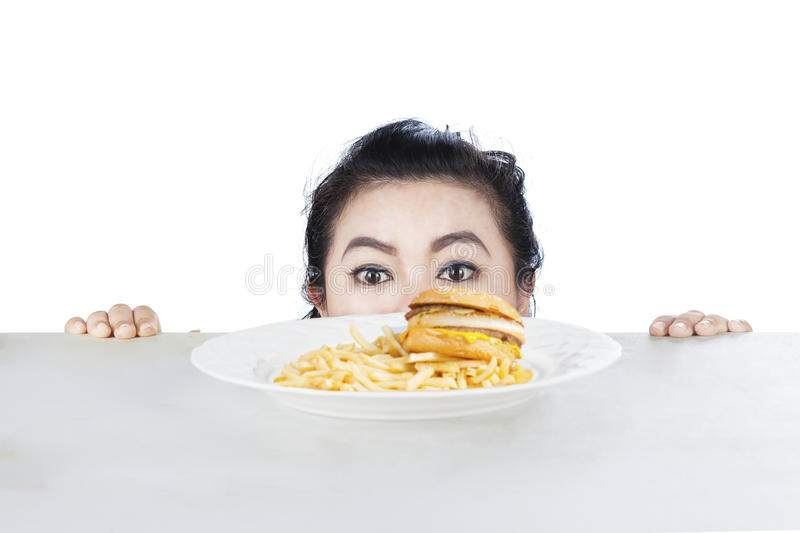 Woman peeping hamburger on a plate. Image of young female is peeping hamburger on the table, isolated on white background stock photography