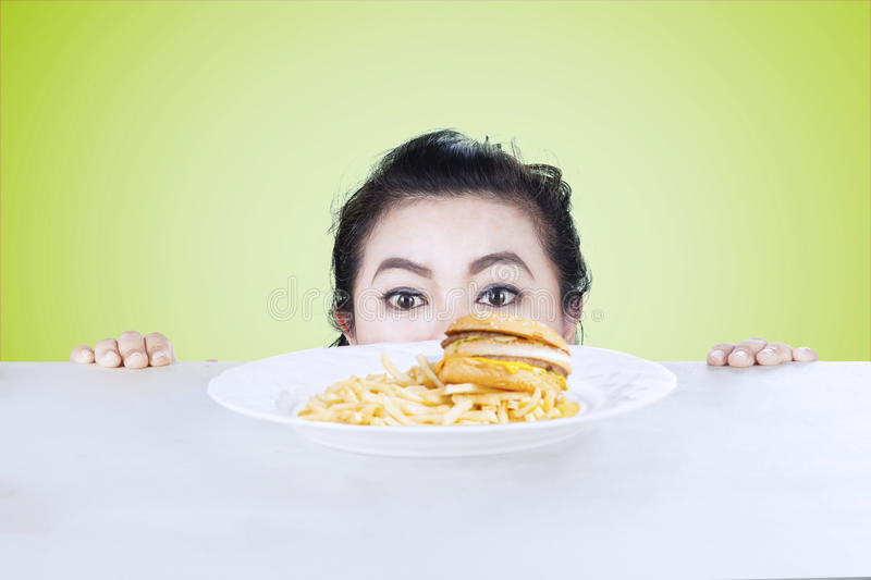 Woman peeping hamburger on studio. Picture of an adult woman is peeping hamburger on the table, shot with green background stock photography