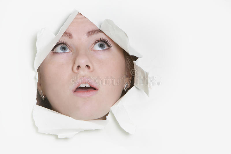 Woman peeping through hole stock photography