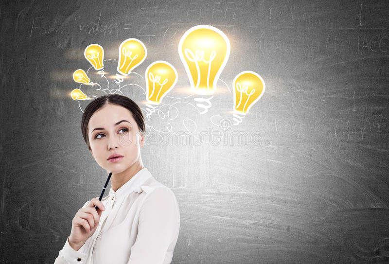 Woman with pen and many light bulbs royalty free stock photo