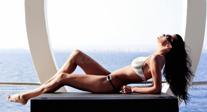 Woman with perfect body. Lying and relaxing on yacht stock photography