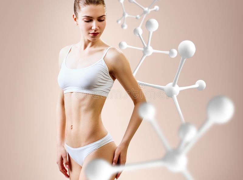 Woman with perfect body near big molecule chain. Slimming concept. Improvement of metabolism concept stock photo